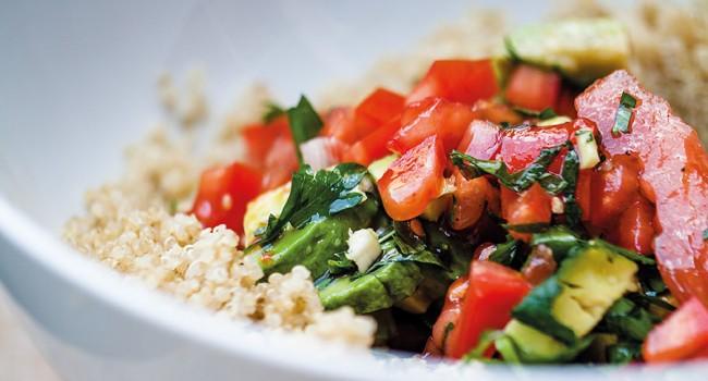 Salade de quinoa, d'avocats et de tomates saupoudrés de persil et de pignons de pin
